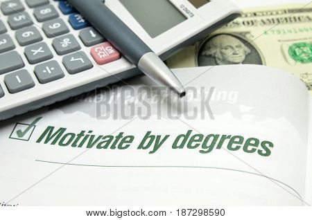 Motivate by degrees printed on book with calculator and pen.