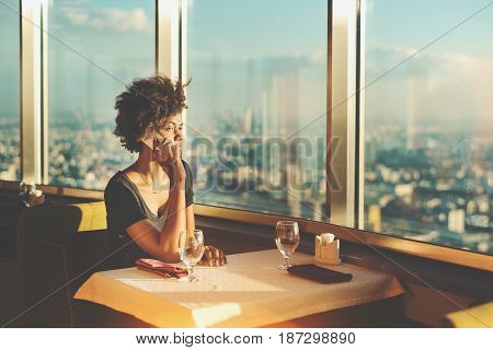 Serious Brazilian teenage female tourist talking on her smartphone with family in roaming while waiting her food in luxury restaurant on top tower with view of cityscape from extremely high point