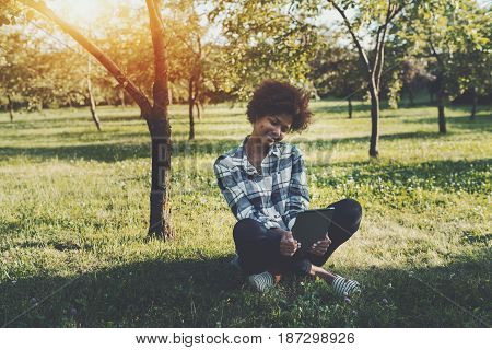 Cheerful afro american teenage girl spending beautiful morning in park with reading eBook young black female student in casual outfit is sitting in public garden and making selfie on digital tablet