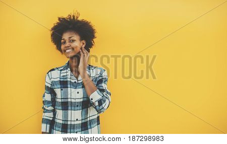 Young biracial student girl with perfect smile and curly afro hair in casual checkered outfit staying in front of solid yellow wall and touching her face with copy space place for your advertising