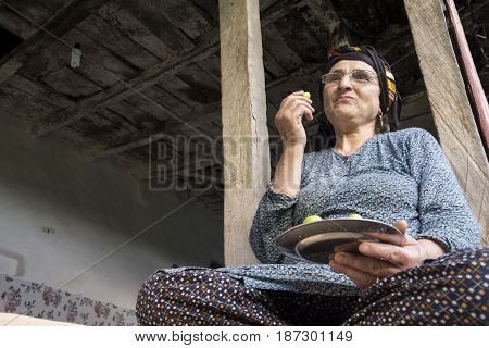 Portrait of a Muslim woman holding plate by hand and eating green plums up view.