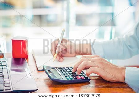 The lifestyle of office workers - young businessman using calculator for finance and tax. Businessmen working at modern business office and writing on note book at wooden table with red coffee cup.