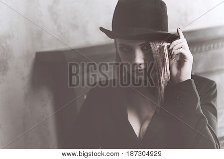 Young attractive girl in a jacket bow tie and bowler hat. Femme fatale. Evening makeup smokey eye. Black and white photography