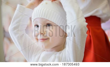 Shopping for kids - sweet girl in a white knitted cap admires in the mirror