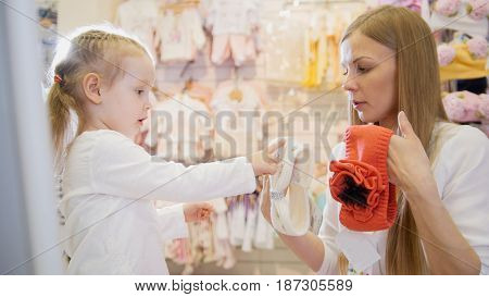 Young woman shows her little daughter white and orange dressing in children's clothing store.