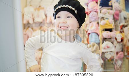 Cute girl in a cute black hat having fun in front of the mirror in the children's clothing store