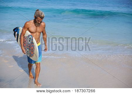 Full-length portrait of an attractive bearded curly man with a surfboard is walking on a beach located on the left side of the frame