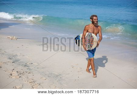 Full-length portrait of an attractive bearded curly man with a surfboard is walking on a beach located on the right side of the frame