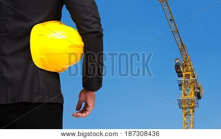 back view of smart construction manager with yellow safety helmet business industrial concept on yellow construction tower crane with blue sky background.