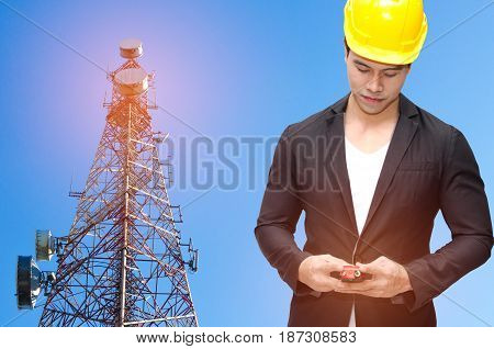 smart construction manager with walkie-talkie or two way radio in hand and yellow safety helmet with telecommunication tower with blue sky background technology business and industrial concept.