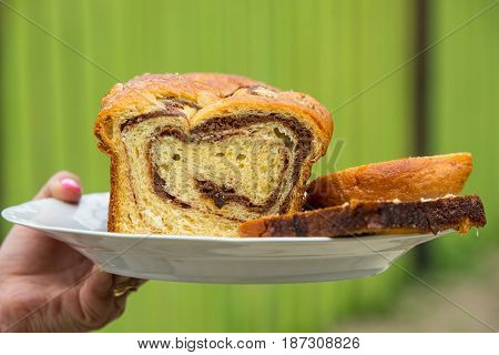 Woman hand holding sponge cake on a plate outdoor