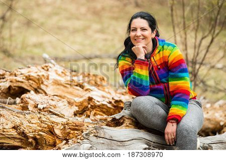 Cheerful woman sitting on a bark tree in nature and holding hand to chin