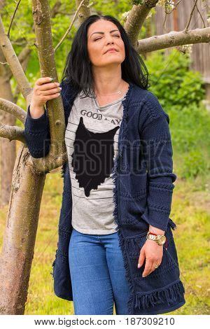 Woman standing with eyes closed near spring tree and feel the nature