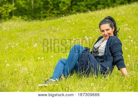 Attractive woman sitting on green grass in nature