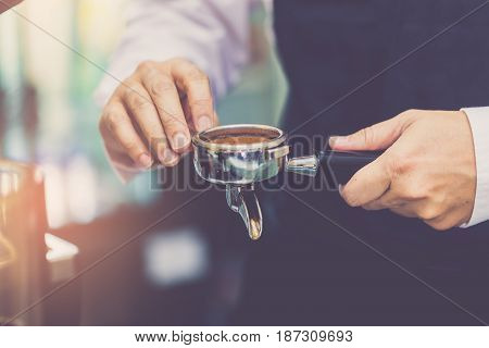 Hand Of Barista Using Tamper With Ground Coffee Into Portafilter In Cafe For Prepare To Make Espress