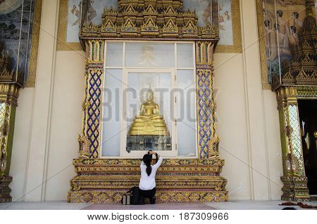 Thai women photographer shooting photo buddha statue at front of ubosot of Wat Wachirathammasatit or wat thung satit temple on February 19 2017 in Bangkok Thailand