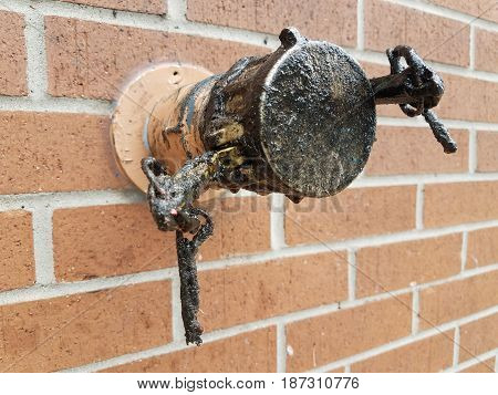 black dripping metal grease pipe and brick wall