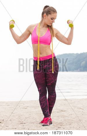 Slim Girl In Sportswear Exercising With Dumbbells On Beach, Concept Of Sports Lifestyle And Slimming