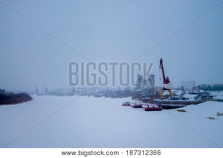 Gantry crane at the dock. Winter. The ice and snow on the river