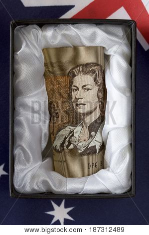 Discontinued Australian one dollar note in a casket with a flag background.
