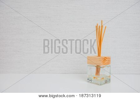 Aroma Glass Bottle And Perfume Stick On Light Background