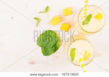 Yellow mango fruit smoothie in glass jars with straw mint leaves mango slices top view. White wooden board background copy space.