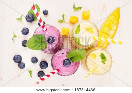 Freshly blended yellow and violet fruit smoothie in glass jars with straw mint leaves mango slices berry top view. Soft white wooden board background.
