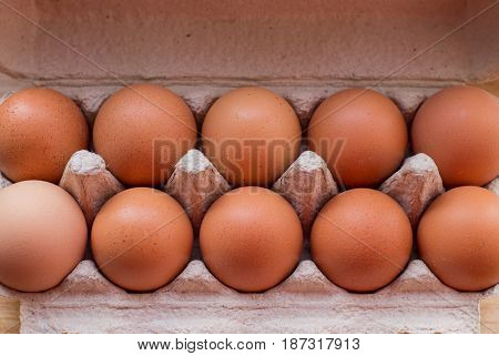 Packing eggs in a cardboard box on the table.
