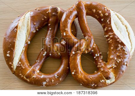 Two salted pretzels on wooden oak table top.