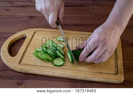 Cut the cucumber with a kitchen knife on the cutting board. Wooden table.