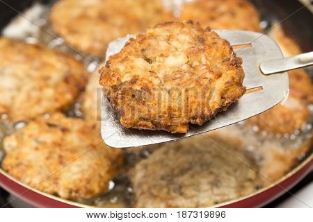 Meat patties are fried in a frying pan .