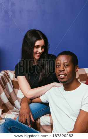 Happy smiling young couple of white woman and black man sit on couch at home, violet wall background with free space. Happiness, togetherness, leisure, fun concept.