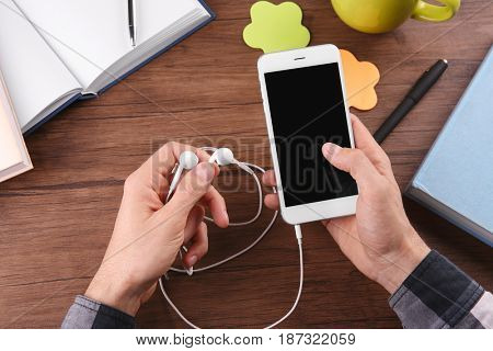 Audio book concept. Young man using smart phone and earphones, close up
