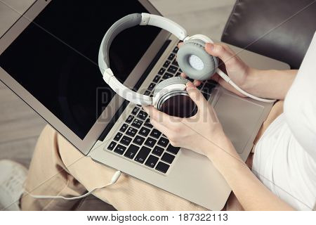Audio book concept. Young woman using laptop with headphones, close up
