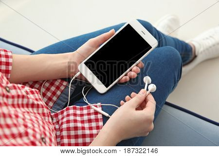 Audio book concept. Young woman holding smart phone and earphones, close up