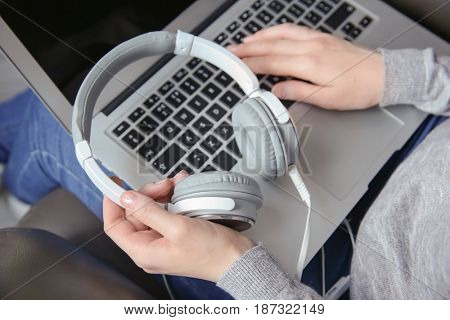 Woman using laptop with headphones while sitting in arm-chair. Concept of audiobook
