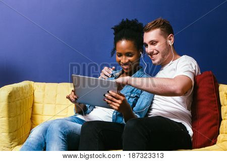 Smiling interracial couple watch photos on tablet and listen to music in earphones sitting on couch at blue wall background. Fun, leisure, great memories and happiness concept.
