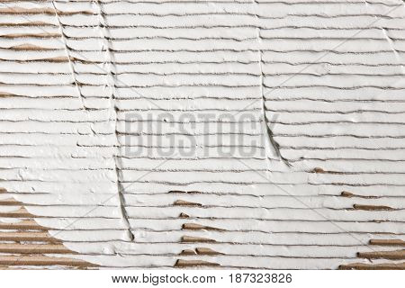White stucco smeared on beige corrugated cardboard, closeup. Repair background with free space for text.