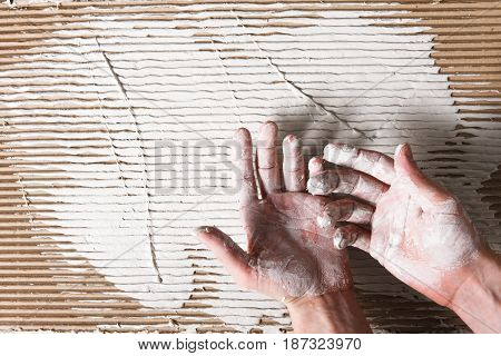 Unrecognizable dirty builder hands with white plaster on stucco textured surface, flat lay. Building background with free space for text.