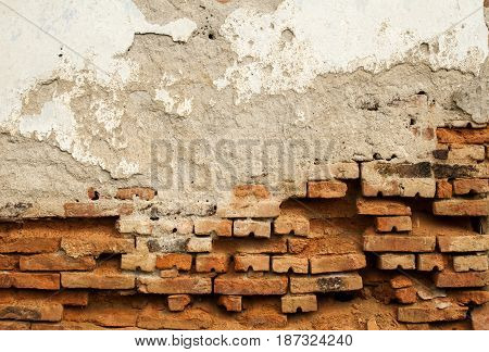 Old weathered grunge brick wall of rustic house with ruinous plaster
