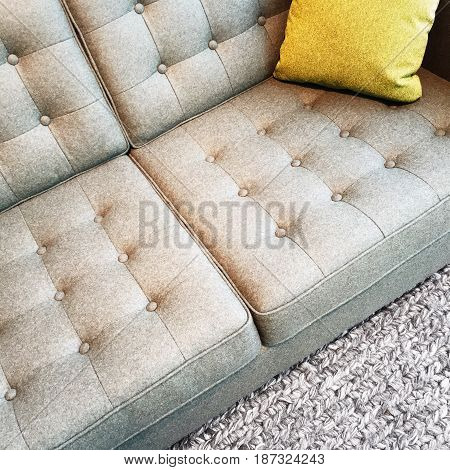 Gray textile sofa with cushion on a knitted rug.