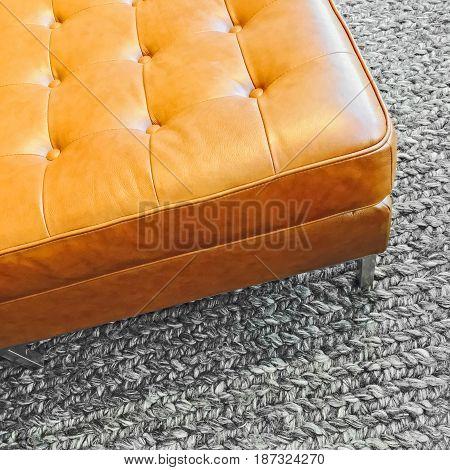 Fashionable leather seat on knitted wool carpet. Contemporary design.