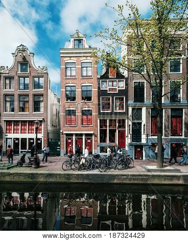 Amsterdam Netherlands - 27 April 2017: Typical narrow houses with large windows and canals with reflection Amsterdam Netherlands.