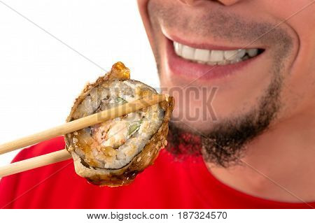smiling young man eating hot sushi roll