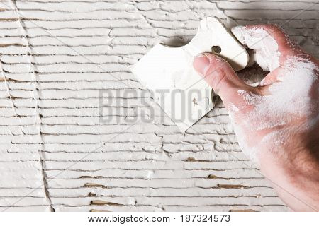 Plastering repair work. Hand with spatula spread white stucco on relief surface. Building textured background with free space for text.