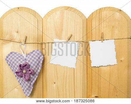 Two jagged note with clothes pegs and a checkered heart of fabric on a cord on wood
