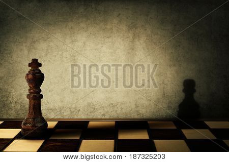 King chess piece casting a shadow of a pawn on a concrete wall. Complex and mismanagement concept. Magical transformation.