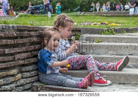 two little girls sitting on the steps outside, the concept of having a rest children