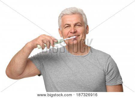 Senior man cleaning teeth on white background