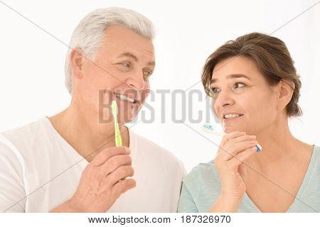 Senior couple cleaning teeth on light background